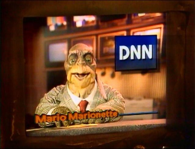 """Fernsehen im Fernsehen: Zu den wiederkehrenden Figuren der DINOS gehört der an Walter Cronkite angelegte Nachrichtensprecher Mario Marionette. Sein englischer Originalname """"Howard Handupme"""" weist selbstreflexiv auf seine Existenz als Handpuppe hin."""