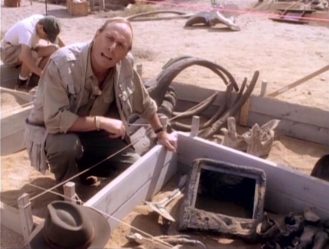 In THE CLIP SHOW stellt sich der Paläontologe Sir David Tushingham (Paxton Whitehead) die Frage, warum sich die Dinosaurier um diesen geheimnisvollen Würfel versammelt haben. In ihrer gnadenlosen Medienkritik kommt das Fernsehen bei den DINOS als Medium der Verdummung und Massenmanipulation nicht gerade gut weg.